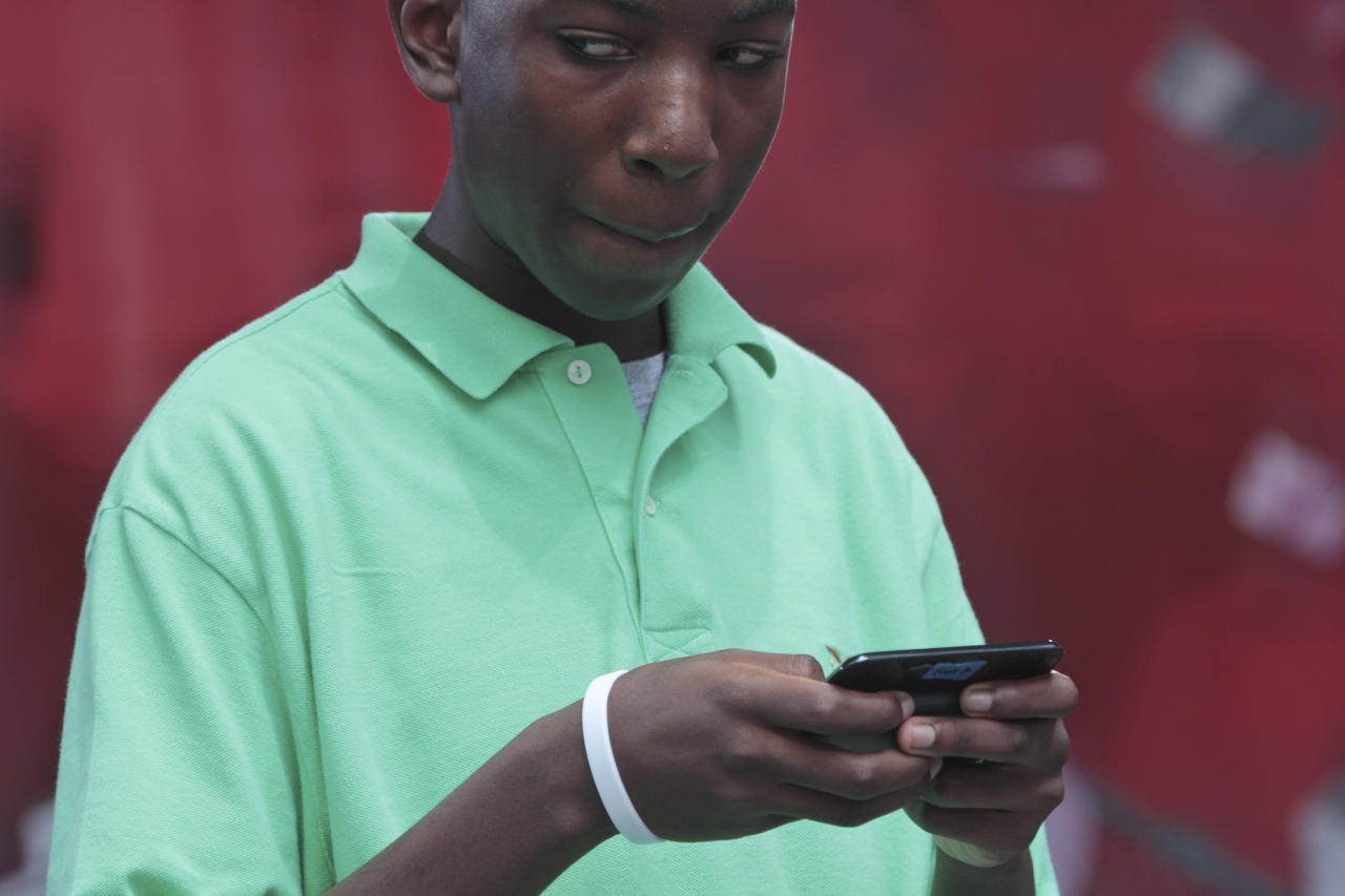 Kent Augustine, of Jamaica, N.Y., looks at his competition while texting during the 2012 LG U.S. National Texting Championship, Wednesday, Aug. 8, 2012 in New York. (AP Photo/Mary Altaffer)