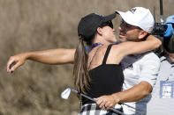 Sergio Garcia, of Spain, gets a kiss from his wife, Angela Akins, after Garcia made a hole in one on the fourth hole to win his playoff against Lee Westwood, of England, during a third round match at the Dell Technologies Match Play Championship golf tournament Friday, March 26, 2021, in Austin, Texas. (AP Photo/David J. Phillip)