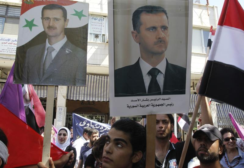 """Supporters of Syria's President Bashar al-Assad wave his posters during a rally in front of the parliament building under the slogan """"No aggression on Syria"""", in Damascus September 17, 2013. REUTERS/Khaled al-Hariri (SYRIA - Tags: POLITICS CONFLICT CIVIL UNREST)"""