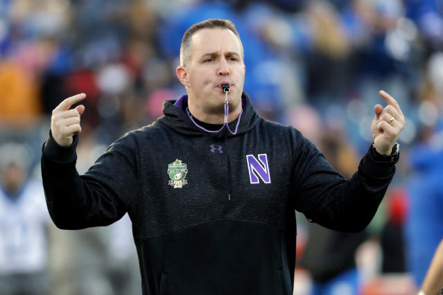 FILE - In this Dec. 29, 2017, file photo, Northwestern head coach Pat Fitzgerald watches his players warm up before the Music City Bowl NCAA college football game against Kentucky, in Nashville, Tenn. College Football Hall of Fame member Pat Fitzgerald was an All-America linebacker at Northwestern and has been head coach there since 2006. He fit the category of star player and student, and he now gets to work with similar youngsters, the vast majority of whom won't be heading to the pros. (AP Photo/Mark Humphrey, File)
