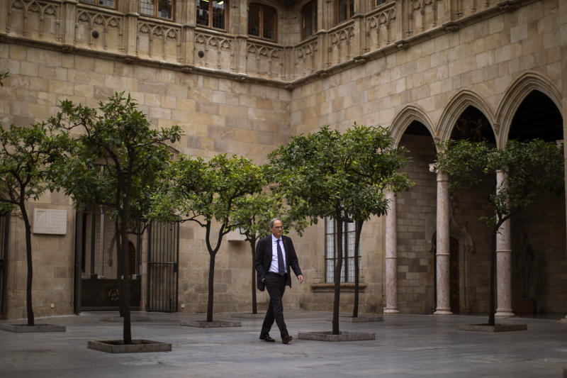Catalan regional president Quim Torra walks at the Palace of the Generalitat, the headquarters of the Government of Catalonia, ahead of an interview with The Associated Press in Barcelona, Spain, Monday, Oct. 21, 2019. The leader of Catalonia says that the massive protests that have often spiraled into violent clashes with police this week won't cease until the Spanish government accepts to listen to separatists' demands. (AP Photo/Emilio Morenatti)