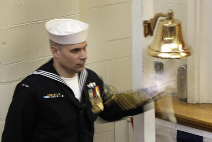 """A sailor rings a bell at the conclusion of the decommissioning ceremony for the fire-damaged USS Miami nuclear submarine at Portsmouth Naval Shipyard, Friday, March 28, 2014, in Kittery, Maine. Rear Adm. Ken Perry, commander of the submarine Group Two in Groton, Conn., where the sub was based, acknowledged the seriousness of the event, but told the crowd they were there to celebrate the submarine and its crew's achievements. """"This is a tribute. This is a celebration of the ship's performance and the superb contributions to the nation's defense and this is how we're going to treat it. So I expect to see some smiles out there,"""" he said. (AP Photo/Robert F. Bukaty)"""