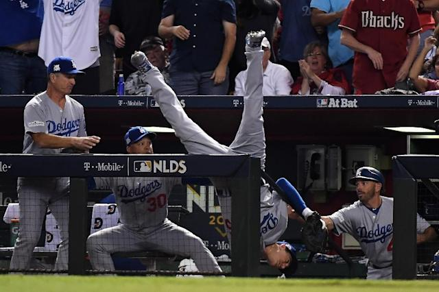 Cody Bellinger of the Los Angeles Dodgers tumbles into the dugout after catching a foul ball during the fifth inning of their National League Divisional Series game three against the Arizona Diamondbacks, in Phoenix, Arizona, on October 9, 2017 (AFP Photo/Norm Hall)