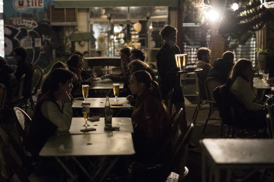People enjoy drinks at a bar terrace in Marseille, southern France, Saturday, Oct. 17, 2020. France is deploying 12,000 police officers to enforce a new curfew that came into effect Friday night for the next month to slow the virus spread, and will spend another 1 billion euros to help businesses hit by the new restrictions. (AP Photo/Daniel Cole)