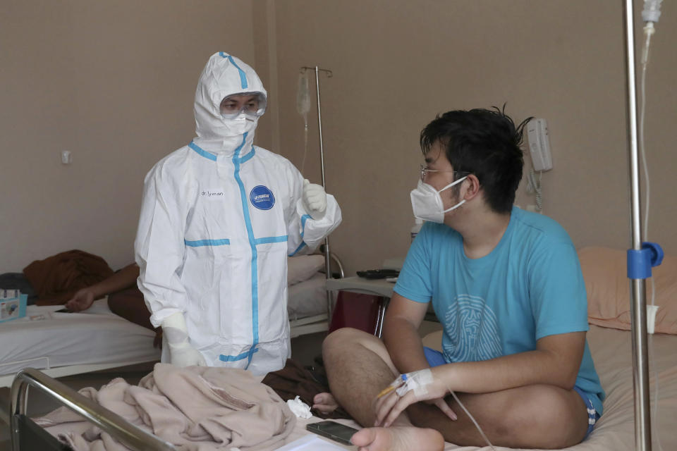 Dr. Irman Pahlepi, left, treats a COVID-19 patient at the Dr. Suyoto General Hospital in Jakarta, Indonesia, on July 29, 2021. Pahlepi is back at work in the hospital, immediately resuming his duties treating COVID-19 patients after recovering from an infection himself, for the second time. With numbers of infections in Indonesia skyrocketing and deaths steadily climbing, health care workers are being depleted as the virus spares nobody, Pahlepi felt he had no option but to jump right back in. (AP Photo/Tatan Syuflana)