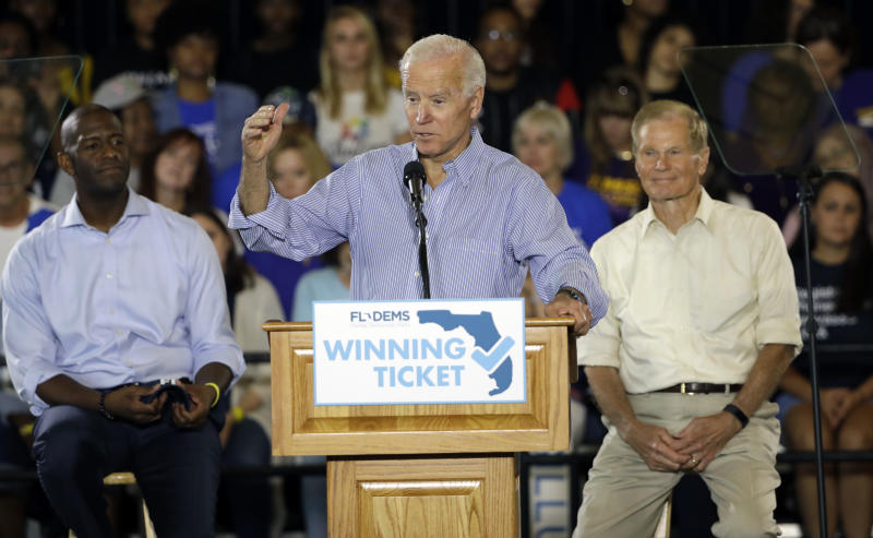 In this Oct. 22, 2018 photo former Vice President Joe Biden speaks during a campaign rally for Florida Democratic gubernatorial candidate Andrew Gillum, left, and U.S. Sen. Bill Nelson, D-Fla., at the University of South Florida in Tampa, Fla. In the past, Florida's top races were tug-of-wars over taxes and education and insurance. This time around the governor's race is a proxy battle between President Donald Trump, who brought GOP gubernatorial nominee Ron DeSantis to prominence, and Democrats who oppose him. (AP Photo/Chris O'Meara)