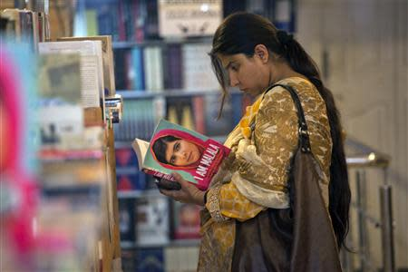 """A woman browses a copy of Malala Yousufzai's book """"I am Malala"""" at a book store in Islamabad"""