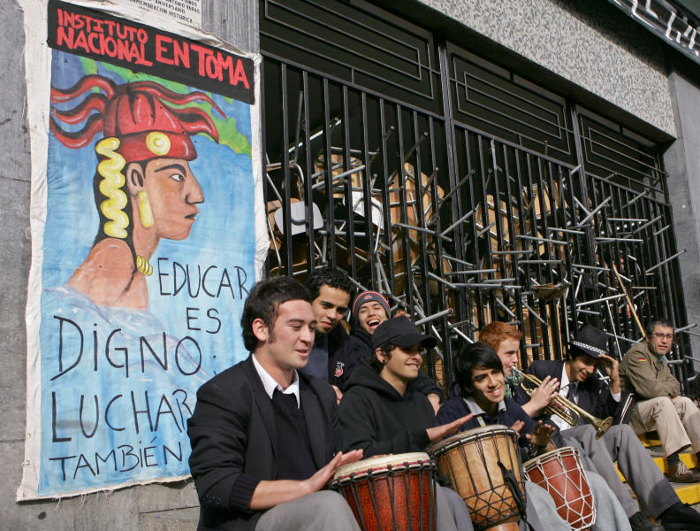 """FILE - In this May 31, 2006 file photo, high school students play music outside the Instituto Nacional high school, which they blocked with chairs and tables in Santiago in Chile. The poster reads """"To educate is honorable, to struggle is as well."""" Starting with high-school students in 2006, then university students five years later, Chile has been hit by regular, large-scale protests led by young people that have won concessions from the government. (AP Photo/Santiago Llanquin)"""