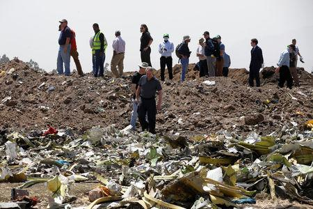 American civil aviation and Boeing investigators search through the debris at the scene of the Ethiopian Airlines Flight ET 302 plane crash, near the town of Bishoftu