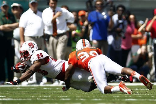 North Carolina State's Tony Creecy (26) stretches for extra yardage as Miami's Antonio Crawford (39) tackles him during the first half of an NCAA college football game in Miami, Saturday, Sept. 29, 2012. (AP Photo/J Pat Carter)