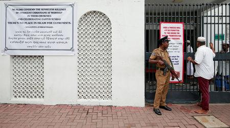 Sri Lankan police officer stand guard in front of a mosque as a Muslim man walks past him during the Friday prayers at a mosque, five days after a string of suicide bomb attacks on Catholic churches and luxury hotels across the island on Easter Sunday, in Colombo, Sri Lanka April 26, 2019. REUTERS/Dinuka Liyanawatte