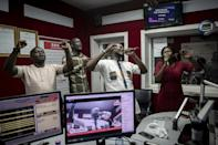 People pray and sing during a worship radio show at Accra FM station in Accra