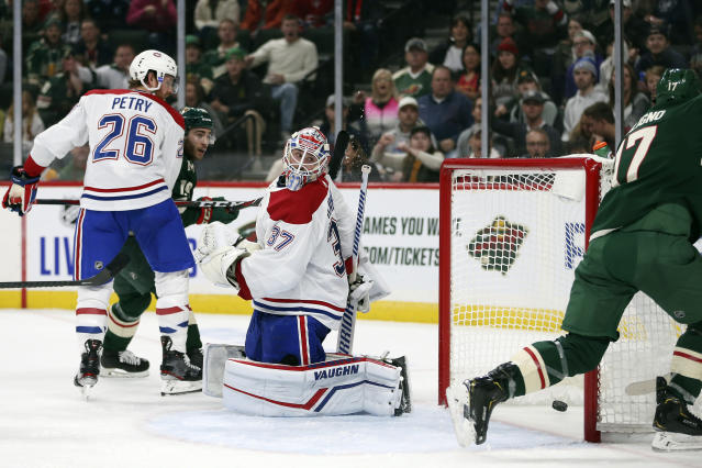 Montreal Canadiens' goalie Keith Kinkaid (37) looks back at the net after Minnesota Wild's Marcus Foligno, right, scored a goal in the second period of an NHL hockey game Sunday Oct. 20, 2019, in St. Paul, Minn. (AP Photo/Stacy Bengs)