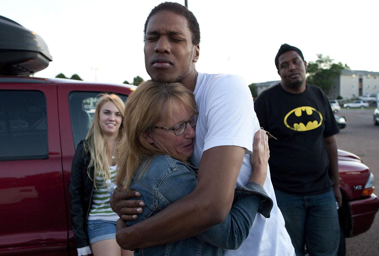 "Judy Goos, second from left, hugs her daughters friend, Isaiah Bow, 20, while eye witnesses Emma Goos, 19, left, and Terrell Wallin, 20, right, gather outside Gateway High School where witness were brought for questioning Friday, July 20, 2012 in Denver. A gunman wearing a gas mask set off an unknown gas and fired into a crowded movie theater at a midnight opening of the Batman movie ""The Dark Knight Rises,"" killing at least 12 people and injuring at least 50 others, authorities said. (AP Photo/Barry Gutierrez)"