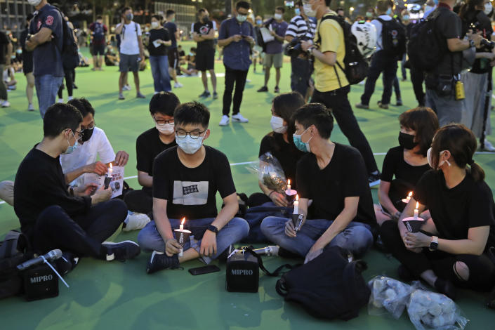 In this June 4, 2020 photo, Hong Kong democracy activist Joshua Wong, second left, holds candle as he joins others for a vigil to remember the victims of the 1989 Tiananmen Square Massacre at Victoria Park in Hong Kong. Wong will face an additional 10 months in jail for participating in an unauthorized Tiananmen vigil held last year to commemorate the 1989 crackdown on protesters in Beijing, as Hong Kong authorities continue tightening control over dissent in the city. (AP Photo/Kin Cheung)