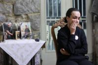 Karlin, wife of a firefighter Charbel Karam and sister of firefighter Najib Hitti, looks on, during an interview with Reuters in Qartaba