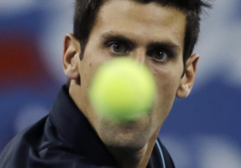 Novak Djokovic, of Serbia, eyes the ball as he returns to Mikhail Youzhny, of Russia, during the men's quarterfinal round at the 2013 U.S. Open tennis tournament, Thursday, Sept. 5, 2013, in New York. (AP Photo/Charles Krupa)