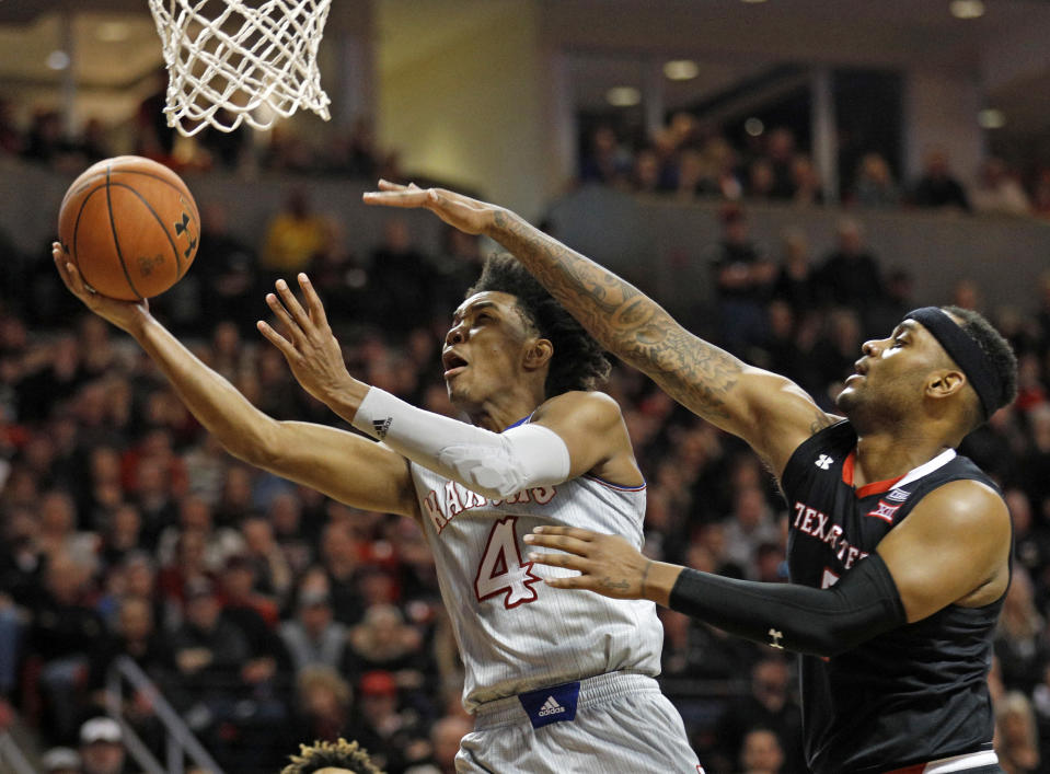 Kansas' Devonte' Graham (4) lays up the ball around Texas Tech's Tommy Hamilton, right, during the second half of an NCAA college basketball game Saturday, Feb. 24, 2018, in Lubbock, Texas. (AP Photo/Brad Tollefson)