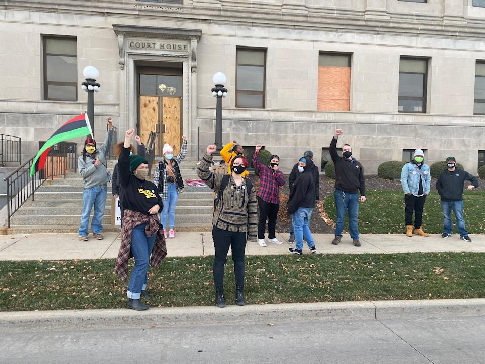 several people stand outside a court house wearing masks and raising their fists