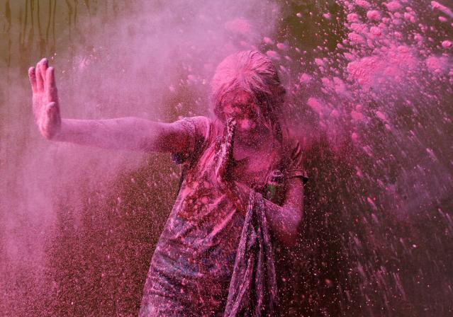 A girl smeared with colours reacts as another girl throws coloured powder at her during Holi celebrations in the southern Indian city of Chennai March 16, 2014. Holi, also known as the Festival of Colours, heralds the beginning of spring and is celebrated all over India. REUTERS/Babu (INDIA - Tags: SOCIETY)