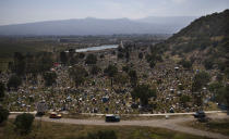 """Graves are decorated with crosses and grass in a section of the municipal cemetery Valle de Chalco amid the new coronavirus pandemic, on the outskirts of Mexico City, Sunday, Oct. 25, 2020. Mexican families traditionally flock to local cemeteries to honor their dead relatives as part of the """"Dia de los Muertos,"""" or Day of the Dead celebrations, but according to authorities the cemeteries will be closed this year to help curb the spread of COVID-19. (AP Photo/Marco Ugarte)"""