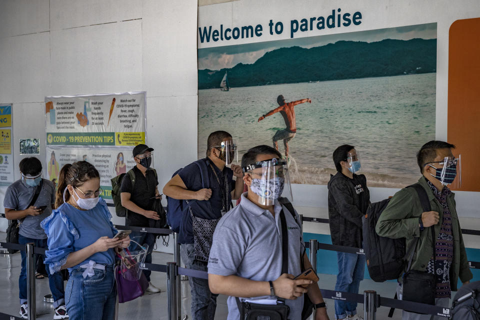 Travelers wearing face masks and face shields to protect against COVID-19 queue upon arriving at Godofredo P. Ramos Airport on September 30, 2020 in Malay, Aklan province, Philippines. The Philippine government has partially reopened the country to domestic travelers in a bid to stimulate the economy and revive a pandemic-hit tourism sector even as coronavirus cases continue to rise. (Photo: Ezra Acayan/Getty Images)