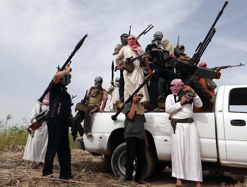 Armed Iraqi tribesmen on the back of a truck on a road north of Ramadi, on May 18, 2013 (AFP Photo/Azhar Shallal)