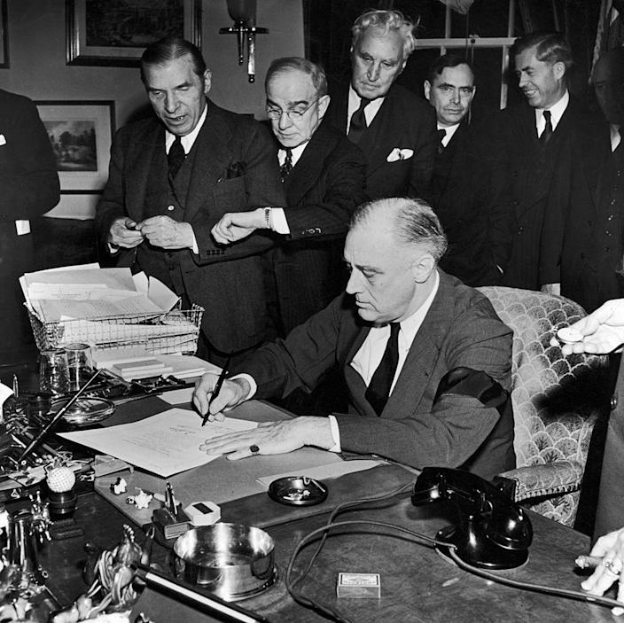 """President Franklin D. Roosevelt (wearing black armband) signing declaration of war as others look on, following Japanese bombing of Pearl Harbor.<span class=""""copyright"""">Thomas D. Mcavoy/The LIFE Picture Collection—Getty Images</span>"""