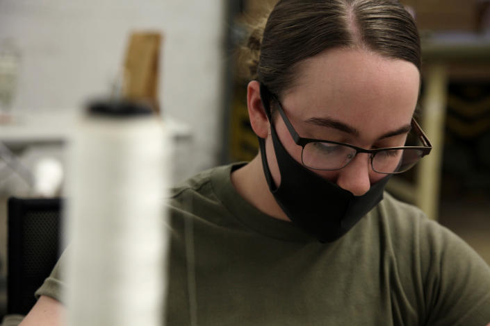 """In this April 17, 2020 photo, a mask covers the face of a U.S. Army Fort Bragg soldier as she sews PPE. Her unit has already constructed thousands of masks since """"Operation Dragon Mask"""" began last week on the North Carolina military installation. (AP Photo/Sarah Blake Morgan)"""