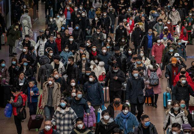 Chinese passengers, most wearing masks, arrive to board trains before the annual Spring Festival at a Beijing railway station.