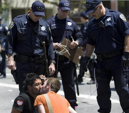 A same sex couple kiss before being arrested in a civil disobedience act in San Francisco, California, May 26, 2009.