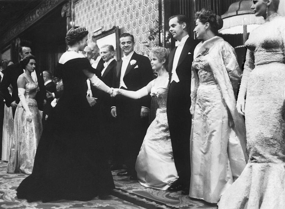 <p>Brigitte Bardot nailed her curtsy—and her outfit—when she met Queen Elizabeth. She wore a satin ball gown with intricate gold embroidery on the bodice and white elbow length gloves. </p>