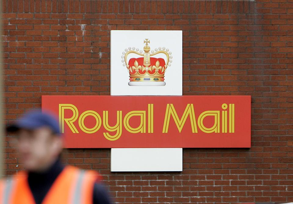 A British Royal Mail logo is seen behind a postal worker walking at a delivery office in London, Monday, Oct. 19, 2009. Royal Mail and the Communication Workers Union (CWU) have resumed talks on pay and working reforms on Monday aimed at avoiding national strikes planned on Thursday and Friday of this week,  while Royal Mail management is planning to hire up to 30,000 temporary workers. (AP Photo/Akira Suemori)