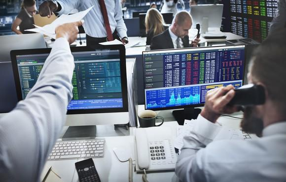 Institutional investors actively trading on their computers at their desks.
