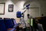 A member of the White House cleaning staff sprays the press briefing room the evening of U.S. President Donald Trump's return from Walter Reed Medical Center