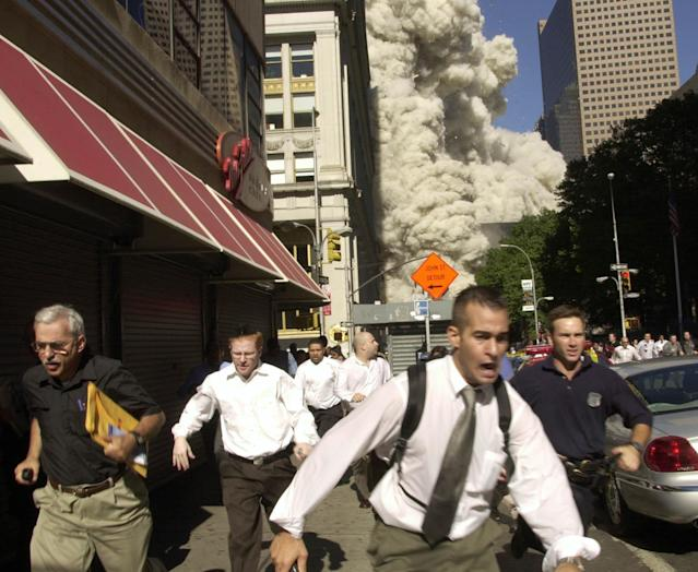 <p>People run from the collapse of World Trade Center on Fulton Street on Sept. 11, 2001. (Photo: Suzanne Plunkett/AP) </p>