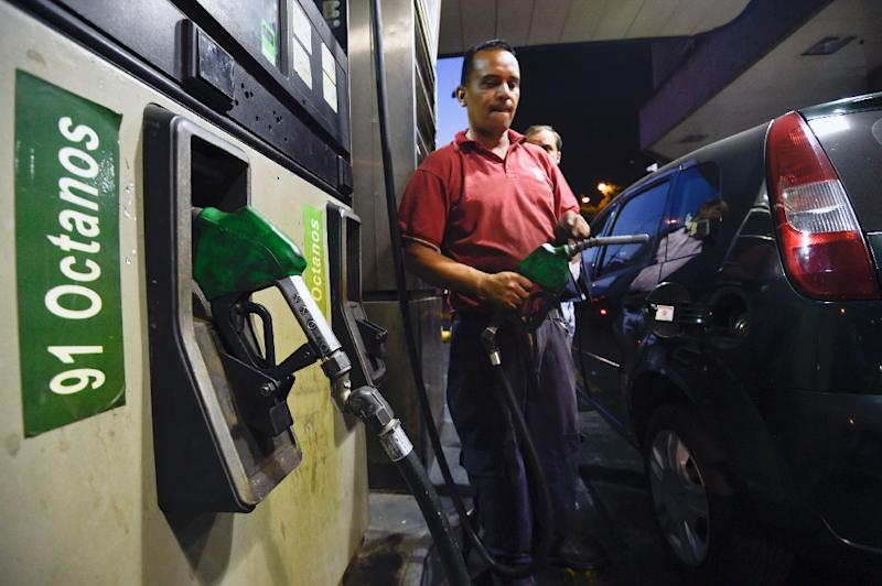 A worker puts gas to a vehicle in Caracas on February 17, 2016 (AFP Photo/Juan Barreto)