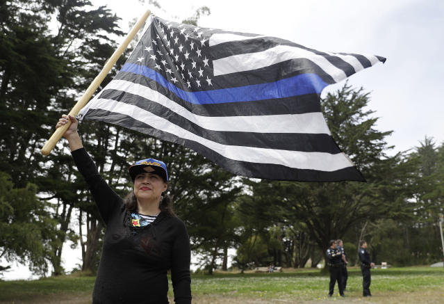 <p>Laura Zulema waves a flag in support of the group Patriot Prayer during a news conference in Pacifica, Calif, Saturday, Aug. 26, 2017. (Photo: Marcio Jose Sanchez/AP) </p>