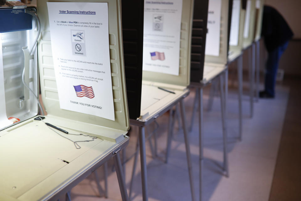 FILE- In this Nov. 8, 2016, file photo a lone voter fills out a ballot alongside a row of empty booths at a polling station in the Terrace Park Community Building on Election Day in Cincinnati. (AP Photo/John Minchillo, File)