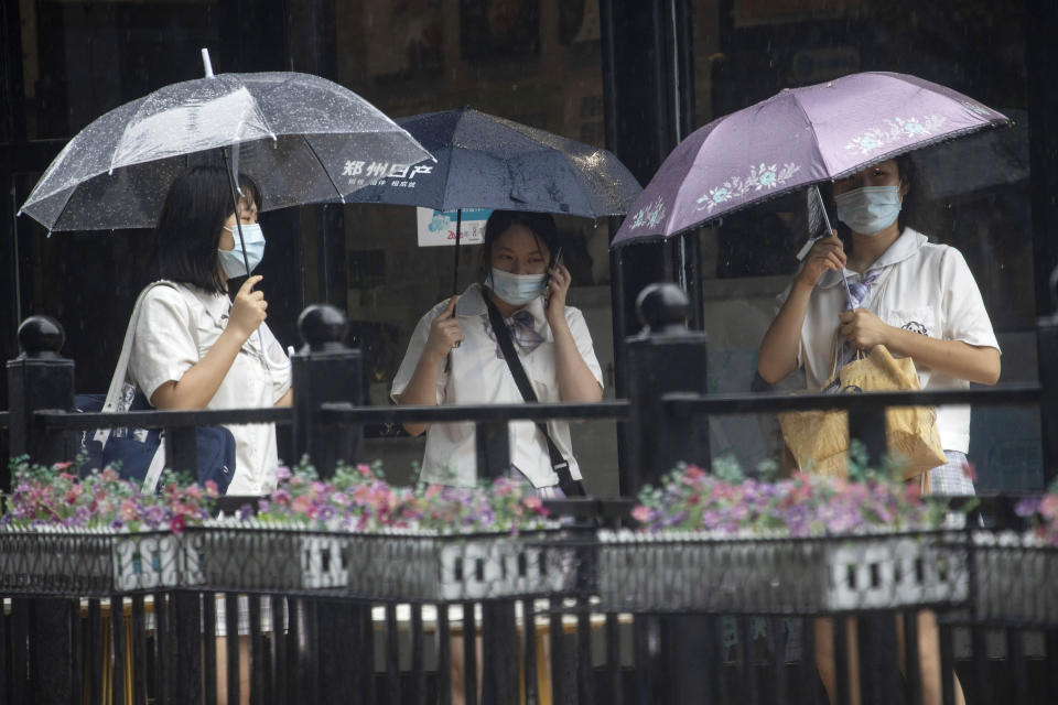 Residents wearing masks to prevent the spread of the coronavirus take cover from a rainstorm in Beijing on Wednesday, Aug. 5, 2020. A downpour in the Chinese capital provided relief from the summer heat. (AP Photo/Ng Han Guan)