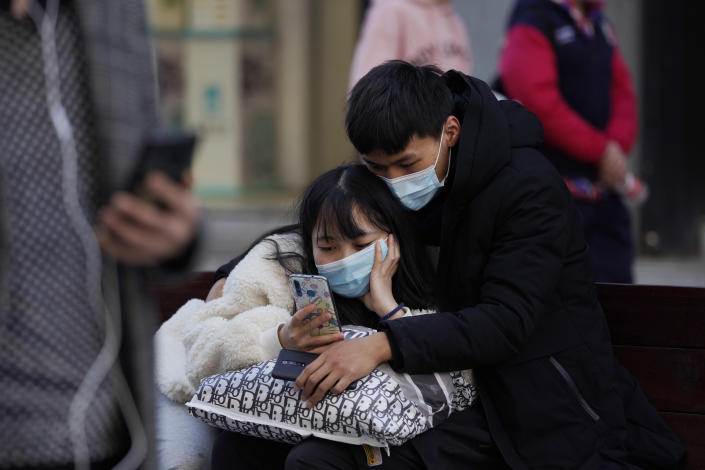 A man and woman wearing masks to help protect themselves from the coronavirus share a smartphone on the street in Wuhan in central China's Hubei province on Thursday, Jan. 14, 2021. A global team of researchers for the World Health Organization arrived Thursday in the Chinese city where the coronavirus pandemic was first detected to conduct a politically sensitive investigation into its origins amid uncertainty about whether Beijing might try to prevent embarrassing discoveries. (AP Photo/Ng Han Guan)