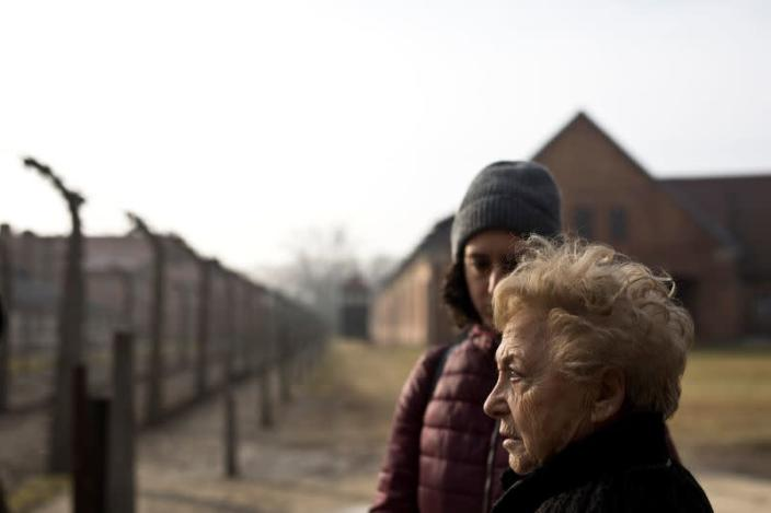 Jona Laks, survivor of Dr. Josef Mengele's twins experiments, and her granddaughter, Lee Aldar stand next to the gate as they as they enter to visit Auschwitz death camp in Oswiecim