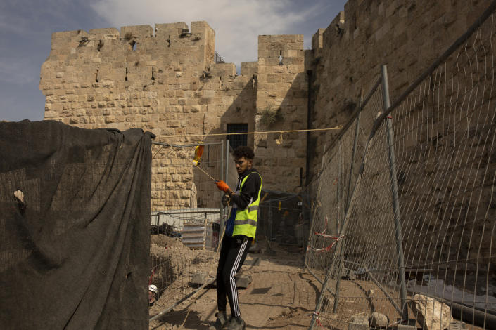 A worker places netting at a construction site inside the Tower of David Museum in the Old City of Jerusalem, Wednesday, Oct. 28, 2020. Jerusalem's ancient citadel is devoid of tourists due to the pandemic and undergoing a massive restoration and conservation project. The Tower of David, the Old City's iconic fortress, contains remnants of successive fortifications built one atop the other stretching back over 2,500 years. (AP Photo/Maya Alleruzzo)