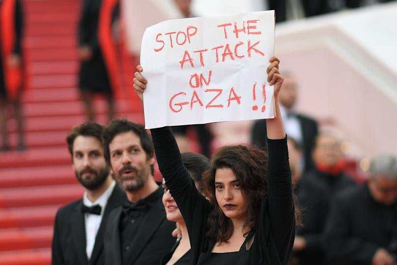 "French-Lebanese actress Manal Issa (R) holds a sign reading ""Stop the Attack on Gaza"" as she arrives on May 15, 2018 with Syrian director Gaya Jiji (2ndR) and Greek-South African film director Etienne Kallos (2ndL) for the screening of the film ""Solo : A Star Wars Story"" at the 71st edition of the Cannes Film Festival in Cannes, southern France. / AFP PHOTO / LOIC VENANCE"