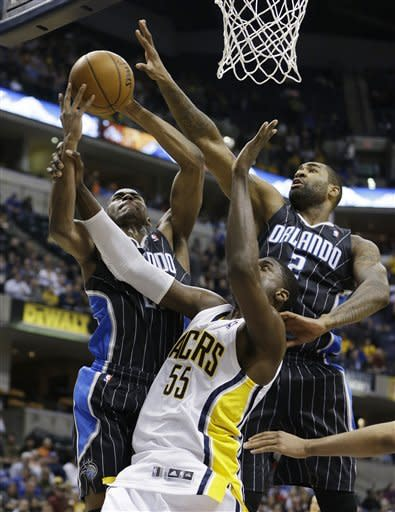 Orlando Magic's Moe Harkless (21) and Kyle O'Quinn (2) vie for a rebound against Indiana Pacers' Roy Hibbert (55) during the first half of an NBA basketball game Tuesday, March 19, 2013, in Indianapolis. (AP Photo/Darron Cummings)