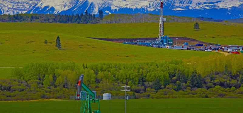 A drilling rig and pump jack with mountains in background.