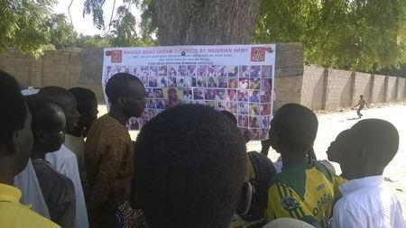 People gather to look at the phoito list of wanted Boko Haram men  posted by the Military on the street of Maiduguri, Borno Sate Nigeria.