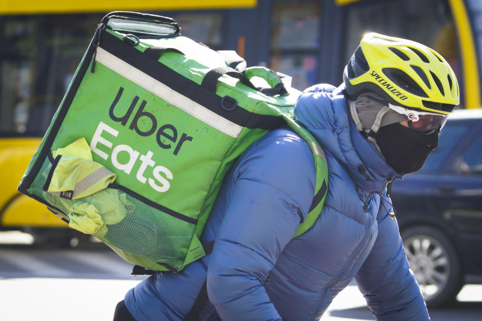 A Uber Eats delivery cyclist is seen wearing a face mask in Warsaw, Poland on March 23, 2020. Polish government spokesman Piotr Muler on Monday announced the administration would not rule out further expanding restrictions to prevent the spread of the coronavirus. The government in the previous week already banned the opening of cinemas, restaurants and bars for at least ten days. People are encouraged to stay at home and gatherings of more than 50 people are prohibited. (Photo by Jaap Arriens/NurPhoto via Getty Images)