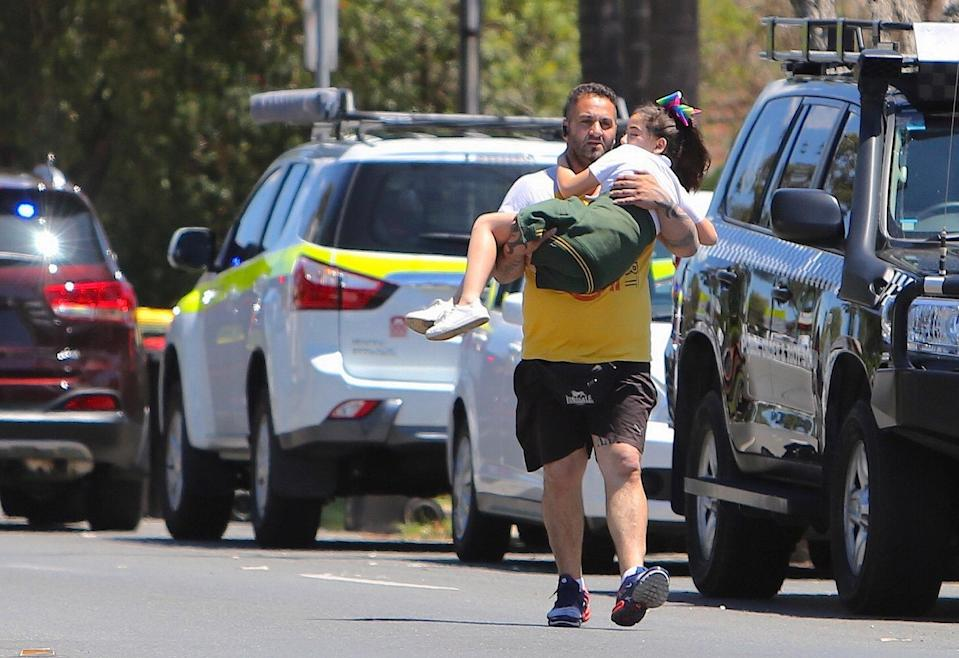 A man carries a child near the scene of the crash (Picture: Reuters)