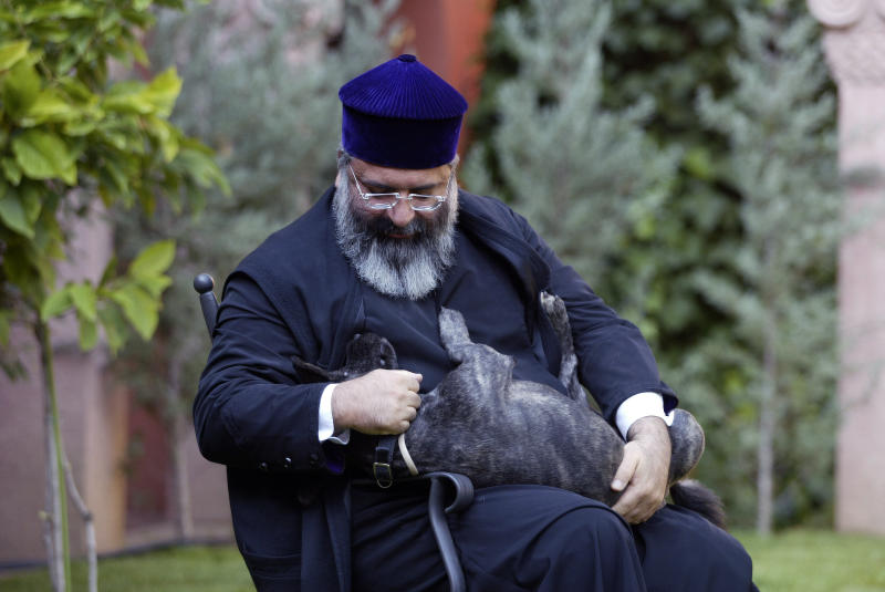 FILE - In this Oct. 21, 2005 file photo, Patriarch Mesrob II, the spiritual leader of Turkey's Armenian Orthodox community, holds his dog in Istanbul. Turkey's state-run Anadolu Agency said Mesrob Mutafyan, 62, the 84th Armenian Patriarch of Constantinople, died Friday, March 8, 2019 at Istanbul's Armenian Surp Pirgic hospital where he was being cared for.(AP Photo, File)